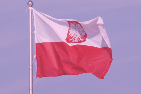 "Photo: ""Polish flag with coat of arms"", by Orem licensed under CC BY-SA 3.0. Hue modified from the original"
