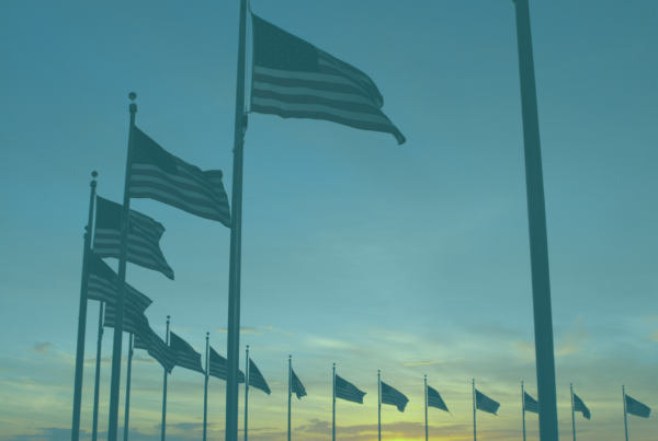 """Photo: """"Flags around monument at sunset"""", by Mommy110710, licensed under CC BY-SA 3.0. Hue modified from the original"""