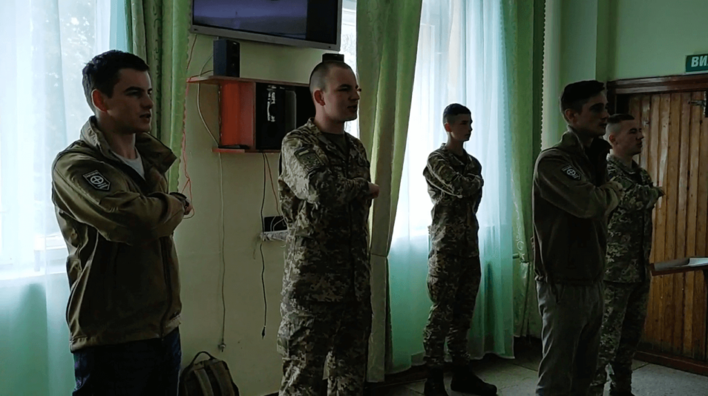 """12 A still from the video posted to Centuria's Telegram shows the individuals leading NAA cadets in the """"Prayer of the Ukrainian Nationalist."""" From left Yuriy Gavrylyshyn, I"""