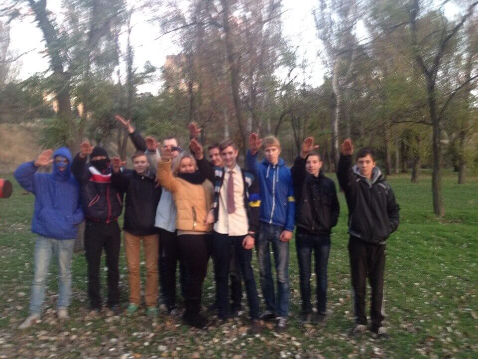 60 Photo of Danylo Tikhomirov (center, wearing a tie) in a group of about a dozen young people making Nazi salutes that was posted to his VK in 2016